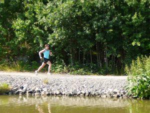 Löpare springer på stig längs vattnet